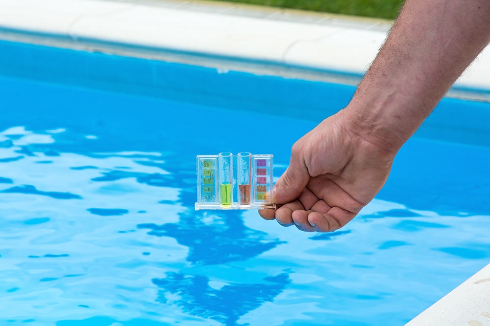 hand holding the pool testing kit above a swimming pool
